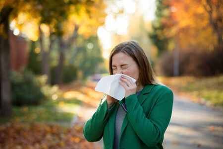 Sick young woman with cold and flu standing outdoors, sneezing, wiping nose with handkerchief, coughing. Autumn street background
