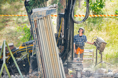 Espoo, FINLAND - JULY 3, 2019: Geothermal heat pump installation in Eco friendly apartment house. Drilling rig in yard. Worker in hard hat drilling a borehole for geothermal heating system.