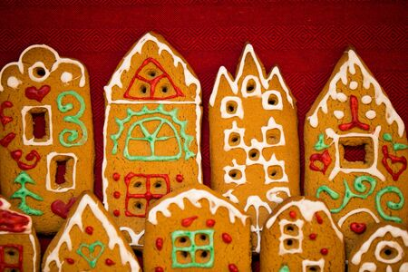 Christmas background. Red table cloth with town of cute gingerbread houses decorated with icing. Standard-Bild