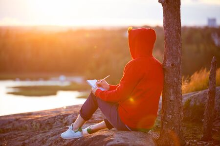 Young man sitting on top of the rock, writing in the notebook.