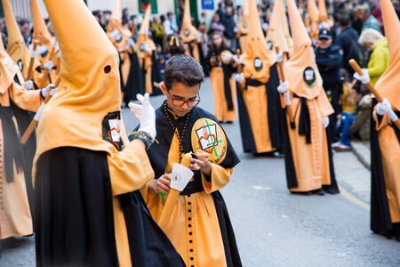 Palma, Spain - April 18 2019: Holy Thursday procession of church brotherhood penitents in conical hoods and robes of different colours  carrying religious statues and accompanied by sombre orchestra