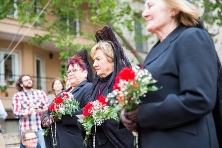 Palma, Spain - April 18 2019: Holy Thursday procession of church brotherhood penitents. Women in black dresses and mantillas standing with flowers in hands