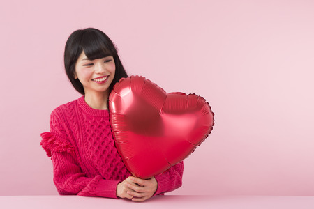 A woman holding a heart shaped balloon