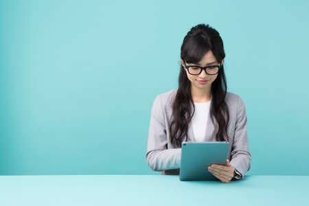 A woman with glasses using a tablet Stockfoto