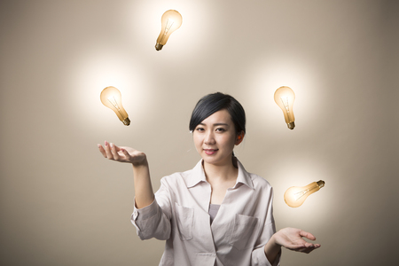Young woman juggling with light bulbs with happy face