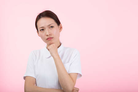 a woman in white who frowns with her hands on her chin in front of a pink background