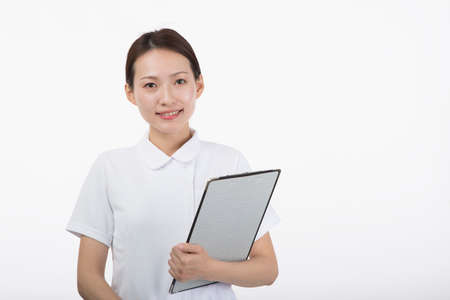 A young woman in a white coat smiling with a questionnaire in front of a white background
