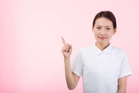 A young woman in white with her index finger up and smiling in front of a pink background.