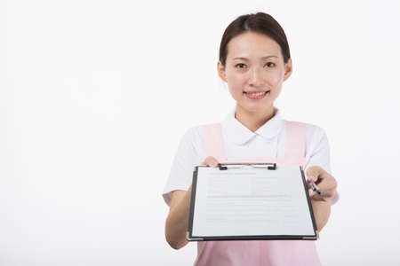 A young woman in a white coat and pink apron smiling with a questionnaire in front of a white background