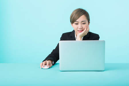A young woman in a black suit smiling as she operates her laptop with a green desk.
