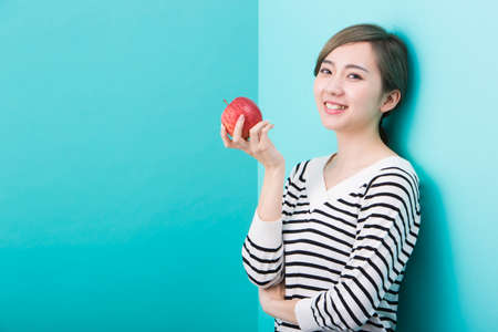 A young woman smiling with a red apple in her hand in front of a blue-green background.
