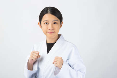 A young woman with dark hair wearing a white dress in front of a white background, wearing a black belt, and posing for fighting.