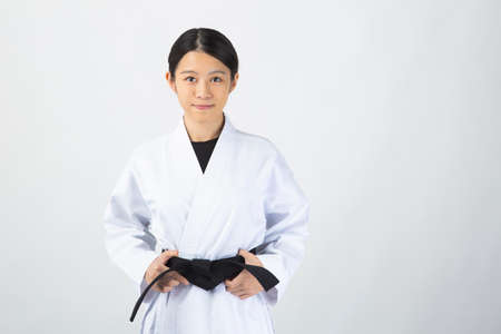 A young woman with dark hair wearing a white dress in front of a white background and smiling while holding a black belt.