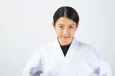 a young woman with dark hair who wears a white dress in front of a white background, tightens her black belt, puts her hand on her waist and has a serious expression