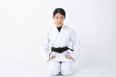 a young woman with dark hair who wears a white dress in front of a white background, tightens her black belt, and sits straight with a serious expression