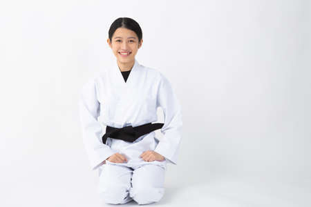 a young woman with dark hair who wears a white dress in front of a white background, tightens her black belt, sits straight and smiles Stock fotó