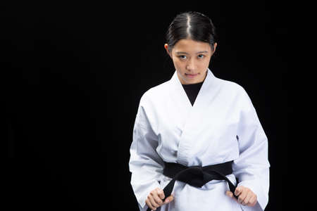 A young woman with dark hair wearing a white dress in front of a white background and staring at the camera while holding a black belt.