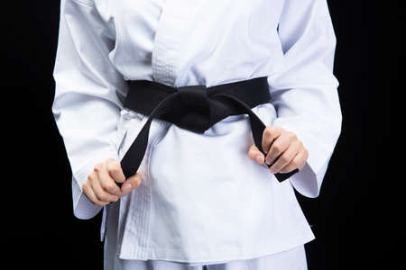 the hand of a woman wearing a white dress and holding a black belt