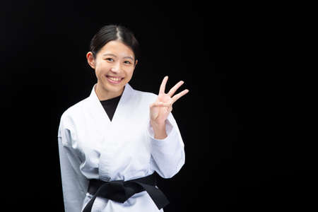 a young woman with dark hair who wears a white dress in front of a black background, tightens her black belt, and smiles with three fingers up