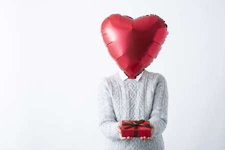 a heart-shaped head woman with a gift box in both hands Stock fotó