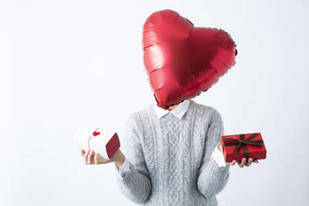 a heart-shaped head woman tilting her head with a gift box in both hands