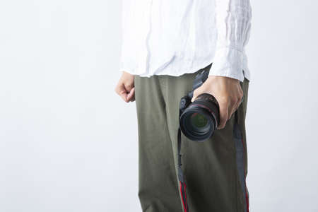 a DSLR camera held in a woman's hand in front of a white background