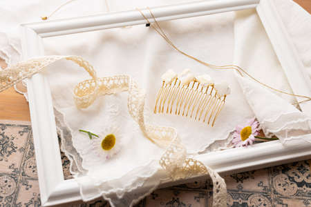Accessories, flowers and ribbons placed on beige cloth