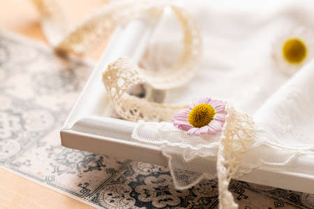 Flowers and ribbons placed on a white picture frame Stock fotó