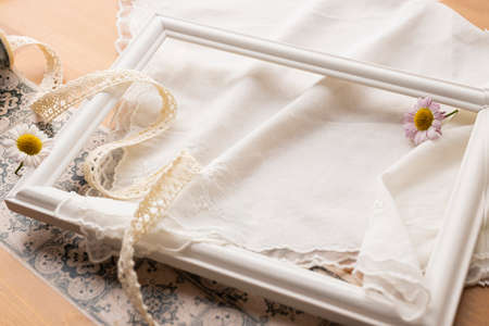 a white picture frame and ribbon placed on a beige cloth Stock fotó