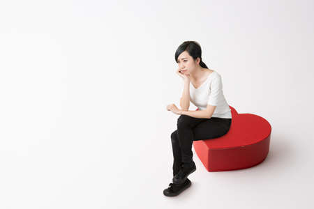a young woman with dark hair who sits with her legs in a heart-shaped red chair and puts her hand on her chin Stock fotó