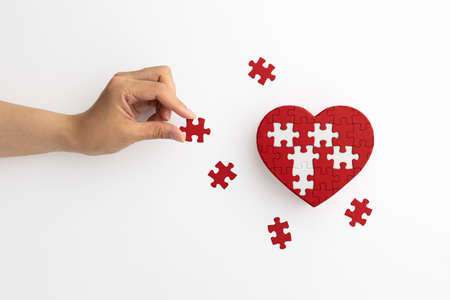 Hands with heart-shaped puzzles and pieces placed on a white background