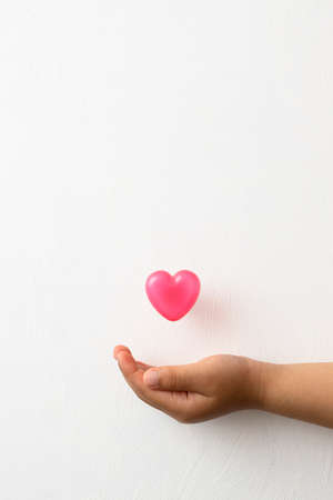 Pink heart-shaped capsule floating on the palm of a child's hand on a white background