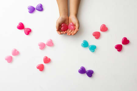 a colorful heart-shaped capsule on a white background and a pink heart-shaped capsule wrapped in both hands Stock fotó
