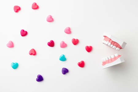 An oral model on a white background and a colorful heart-shaped capsule