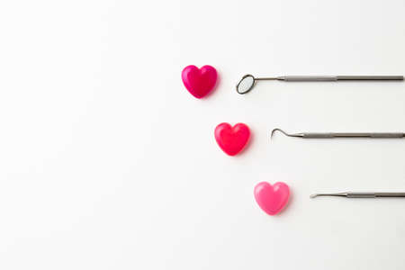 Dental instruments and colorful heart-shaped capsules placed on a white background