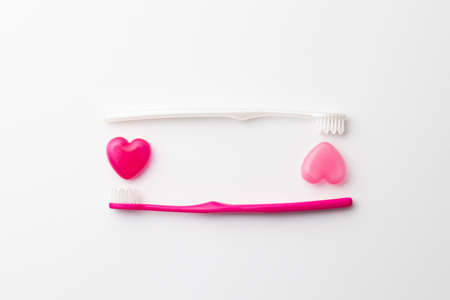 Toothbrush and heart-shaped capsule on a white background