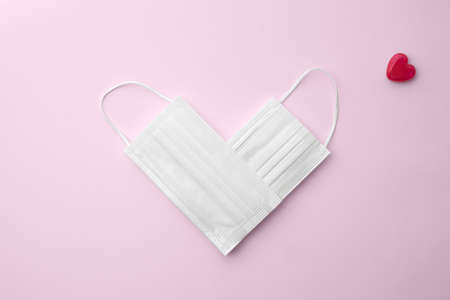 a white mask placed in a heart shape on a pink background Stock fotó