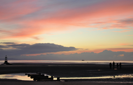 an image taken at the famous anthony gormleysanother placein crosby liverpool,you can see the silhouett of the pipeline running out to sea and a gathering of people looking at one of the 100 iron men just after sunset with a beautiful pink and blue sky Stock Photo