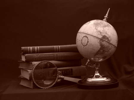 Globe with magnifying glass and books