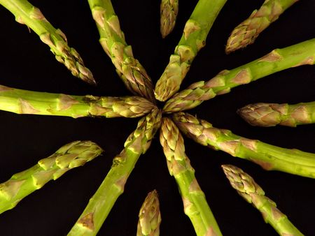 Asparagus Spears moving toward each other on black.