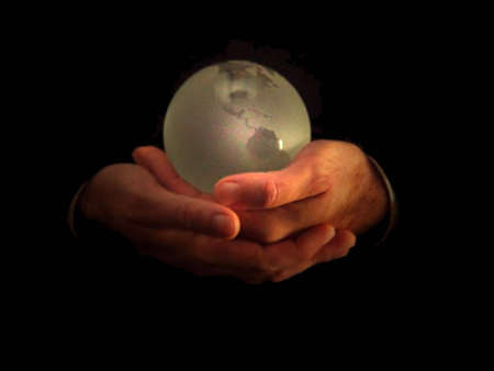Man holding frosted world globe gently in his hands.