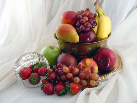 Brass bowl overflowing with grapes, nectarines, apples, pears, bananas, strawberries and grapes.