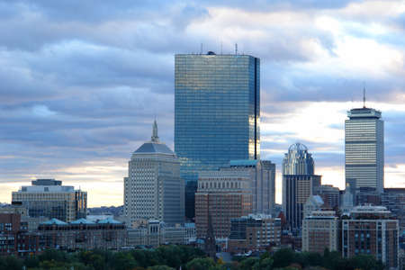 Sun setting on Boston skyline on a cloudy day.