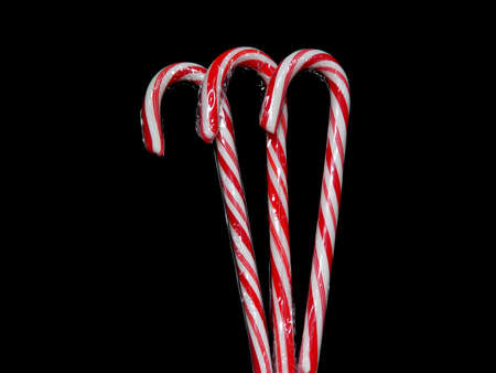 stuffer: Three candy canes on a black background.