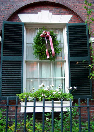 pine wreaths: beautiful arched window frame with shutters and christmas wreath, flower box and old wrought iron fence in boston on beacon hill