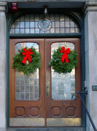 two pine wreaths with red ribbons on brown wooden doors