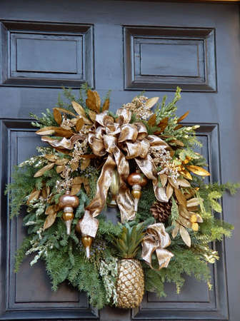 wreath hanging outside on door with gold ribbon, pine cones, pineapple