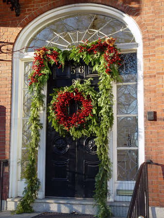 a beautiful red and green xmas wreath hangs in the middle of a door surrounded by pine garland and more holly berries Imagens