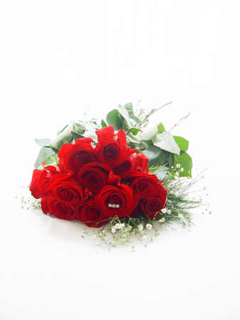 Dozen red rose with trinity diamond ring in the center of one rose