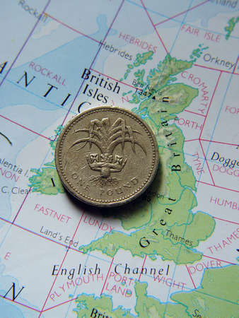 Backside of a British One Pound Coin on Great Britain map.